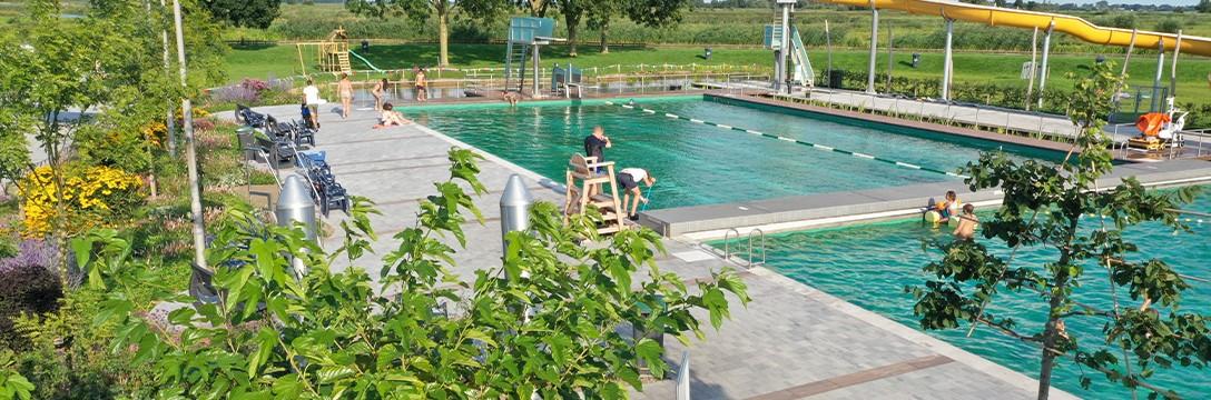 Lichte en stroeve bestrating rond uniek natuurgezuiverd zwembad